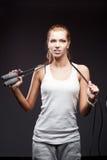 Meisje met springen-kabel op donkere achtergrond Stock Afbeelding