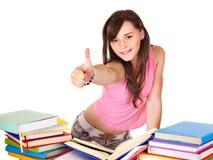 Meisje met stapelboek dat duim toont. stock foto