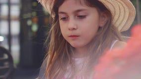 Meisje met strohoed die haar sandwich eten en met ballon spelen stock footage