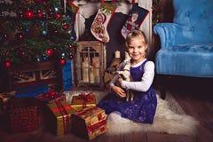 Meisje met stuk speelgoed paard in Kerstmisruimte royalty-vrije stock afbeeldingen