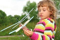 Meisje met stuk speelgoed vliegtuig in handen openlucht Stock Foto