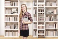 Meisje met tablet in een huisbibliotheek met een ladder Royalty-vrije Stock Afbeeldingen