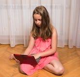 Meisje met tabletpc thuis Stock Afbeelding