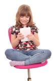Meisje met tabletzitting Stock Fotografie