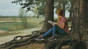 Meisje met tabletzitting tegen boom in in openlucht bos langzame motie stock videobeelden
