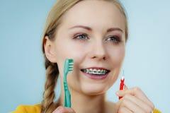 Meisje met tandensteunen die interdental en traditionele borstel gebruiken stock fotografie