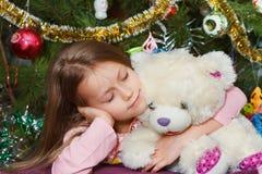 Meisje met teddybeer dichtbij Kerstmisboom Stock Fotografie