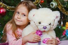 Meisje met teddybeer dichtbij Kerstmisboom Royalty-vrije Stock Afbeeldingen