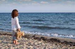 Meisje met teddybeer die zich op strand bevinden Royalty-vrije Stock Foto's
