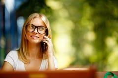 Meisje met telefoon op achtergrond van groene bomen stock fotografie