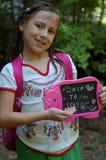 Meisje met terug naar schoolteken Stock Foto's