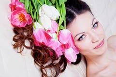 Meisje met tulpenbloemen Stock Foto