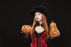 Meisje met twee Halloween pompoen op zwarte Royalty-vrije Stock Afbeelding