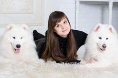 Meisje met twee sneeuw Samoyed Royalty-vrije Stock Foto's