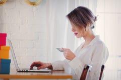 Meisje met vakantiegiften en laptop computer die een creditcard houden stock foto's