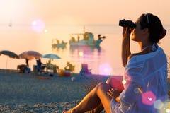 Meisje met verrekijkers op de kust Stock Afbeeldingen