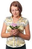 Meisje met viooltjes in een bloempot stock fotografie