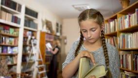 Meisje met vlechten in de bibliotheek stock footage