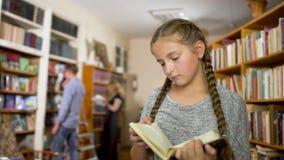 Meisje met vlechten in de bibliotheek stock video