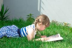 Meisje met vlechten die op het gras liggen en een boek lezen royalty-vrije stock foto's