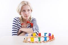 Meisje met vlechten en houten stuk speelgoed Stock Fotografie
