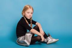 Meisje met vlechten in modieuze kleren op blauwe achtergrond stock afbeeldingen