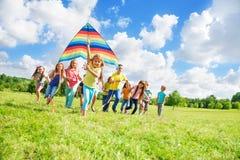 Meisje met vrienden en vlieger Stock Afbeeldingen