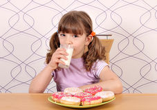 Meisje met zoete donuts en melk Royalty-vrije Stock Foto