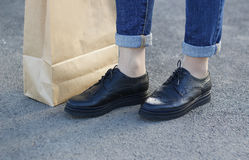 Meisje in mooie schoenentribunes naast een document zak Stock Afbeelding