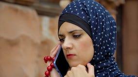 Meisje in moslimkleren die op de telefoon spreken stock footage
