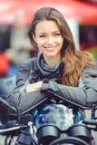 Meisje in motomateriaal met een motorfiets Royalty-vrije Stock Afbeeldingen