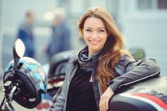 Meisje in motomateriaal met een motorfiets Stock Foto
