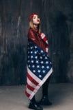 Meisje omvat door Amerikaanse vlag op donkere achtergrond Royalty-vrije Stock Fotografie