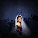 Meisje onder de dekking met een flitslicht Stock Afbeeldingen