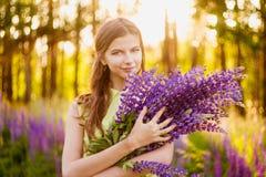 Meisje onder het tot bloei komen lupines Stock Fotografie