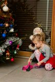 Meisje onder Kerstboom schoonmakende naalden Stock Fotografie