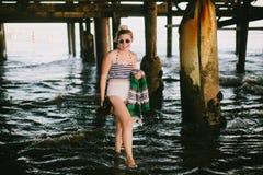 Meisje onder pijler op strand royalty-vrije stock afbeelding