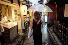 Meisje onder regen in Kyoto stock foto's