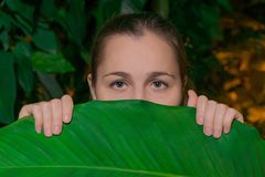 Meisje onder tropische vegetatie stock foto