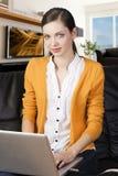 Meisje op bank met laptop, wijst zij op displa Stock Fotografie