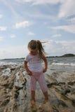 Meisje op bewolkte kust Stock Afbeeldingen