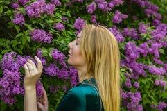 Meisje op de achtergrond van een bloeiende lilac boom royalty-vrije stock afbeelding
