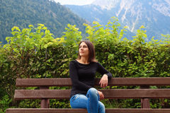 Meisje op de bank op de achtergrond van Alpen Royalty-vrije Stock Afbeelding