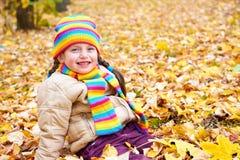 Meisje op de bladeren van de dalingsherfst in park Royalty-vrije Stock Foto