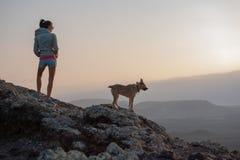 Meisje op de bovenkant van de vulkaan met haar hond royalty-vrije stock foto's
