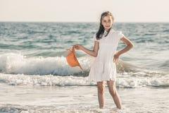 Meisje op de kust die een oranje hoed en een witte kleding dragen stock afbeeldingen