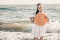 Meisje op de kust die een oranje hoed en een witte kleding dragen royalty-vrije stock foto