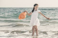 Meisje op de kust die een oranje hoed en een witte kleding dragen stock afbeelding
