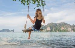 Meisje op de kust die op een schommeling slingeren stock fotografie