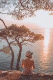 Meisje op de overzeese heuvel in de zonsondergang Stock Fotografie